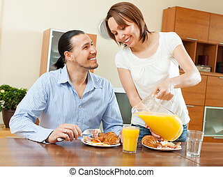 Happy couple having breakfast with croissants