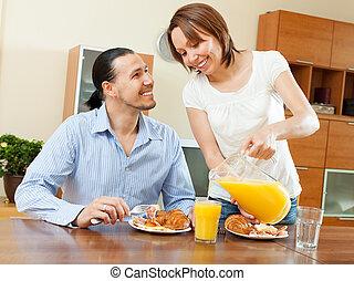 Happy couple having breakfast with croissants