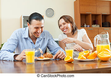 Happy couple having breakfast with juice in morning at home