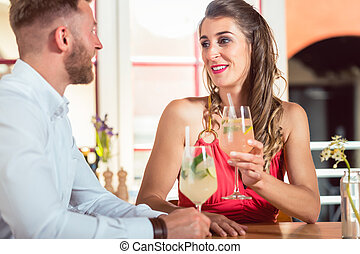 Happy couple having cocktails