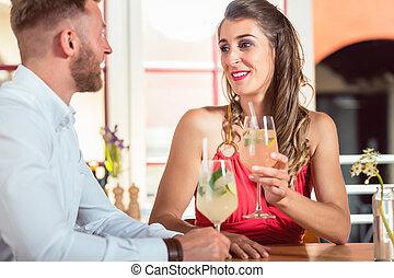Happy couple having cocktails