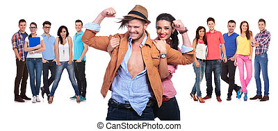 happy couple having fun in front of their large group of friends on white background