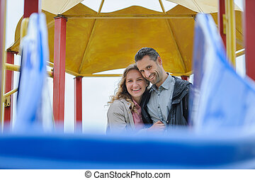 Happy couple having Fun in playground looking at camera