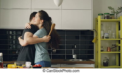 Happy couple having fun in the kitchen fencing with big spoons and embracing each other while cooking breakfast at home