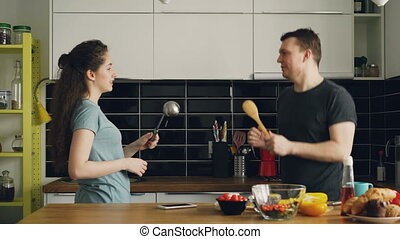 Happy couple having fun in the kitchen fencing with big spoons while cooking breakfast at home