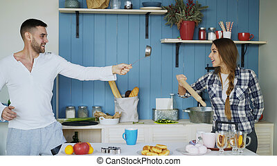 Happy couple having fun in the kitchen fencing with ladle and rolling-pin while cooking breakfast at home