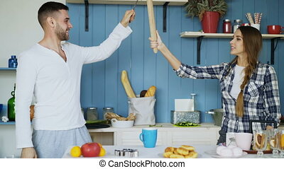 Happy couple having fun in the kitchen fencing with ladle...