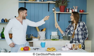 Happy couple having fun in the kitchen fighting with ladle...