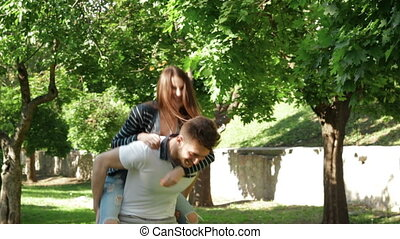 happy couple having fun in the Park and the girl at the hands of guy wears