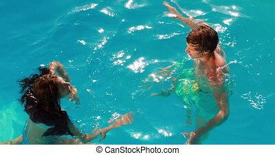 Happy couple having fun in the pool