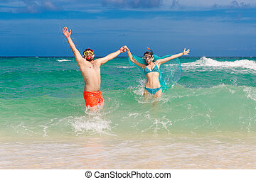Happy couple having fun on the beach of a tropical island. Summer vacation concept.