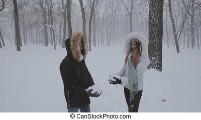 happy couple having fun together throwing snow up - happy...