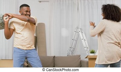 happy couple having pillow fight at new home - moving, ...