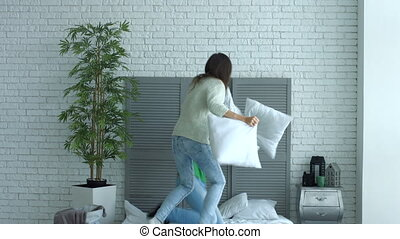 Happy couple having pillow fight in the bedroom - Excited...