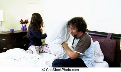 Happy couple having pillow fight