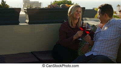 Happy couple having red wine in the balcony at home 4k - ...