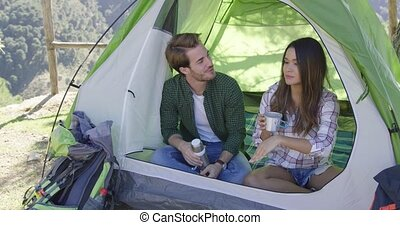 Young happy tourists sitting in tent and drinking tea while having rest in mountains.