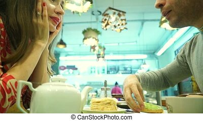 Happy couple having their dessert in a cafe. Man regales girl with a cake