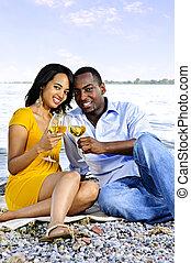 Happy couple having wine on beach - Young romantic couple...