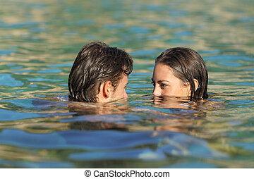 Happy couple heads flirting bathing on the beach