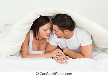 Happy couple hiding under a blanket