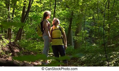 Happy couple hiking in sunny summer forest. 4K zoom in shot