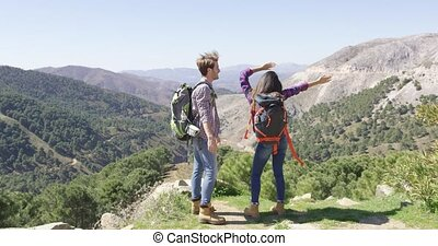 Happy couple hiking - Back view of loving couple having fun...
