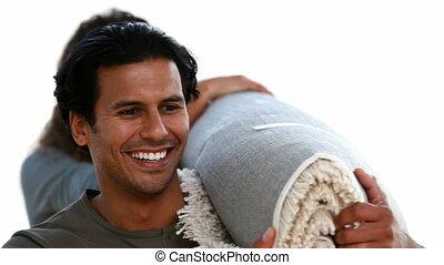 Happy couple holding a carpet
