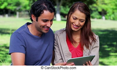 Happy couple holding a tablet computer