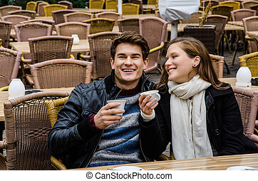 Happy Couple Holding Coffee Cups At Restaurant
