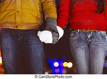 Happy couple holding hands in knitted mittens