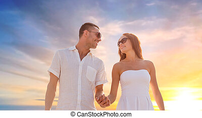 happy couple holding hands over sunset sky