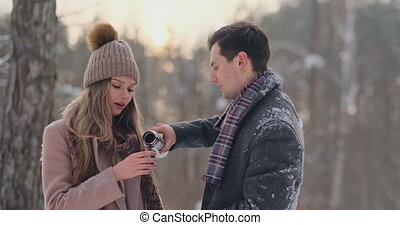 Happy couple holding hot tea cups over winter landscape....