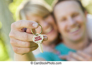 Couple Holding House Key with New Home Text