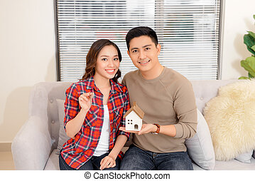 Happy couple holding keys to new home and house miniature - real estate concept