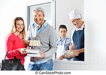 Happy Couple Holding Pasta Packets By Chefs At Window