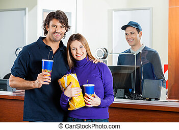 Happy Couple Holding Snacks With Seller At Box Office Counter