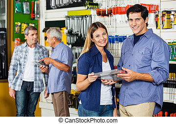 Happy Couple Holding Tool Set In Hardware Store
