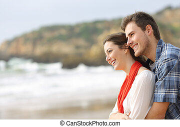 Happy couple hugging and looking at horizon on the beach