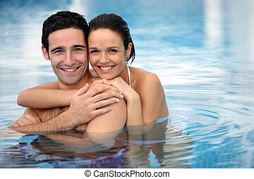 Happy couple hugging in a swimming-pool