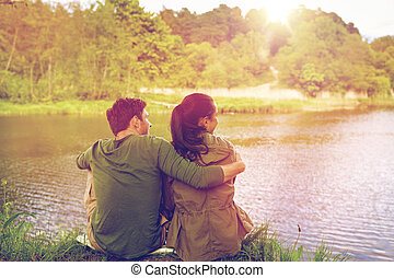 happy couple hugging on lake or river bank - love, travel,...