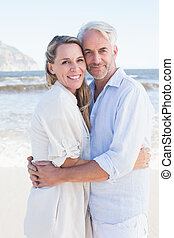 Happy couple hugging on the beach looking at camera
