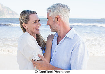 Happy couple hugging on the beach looking at each other on a...