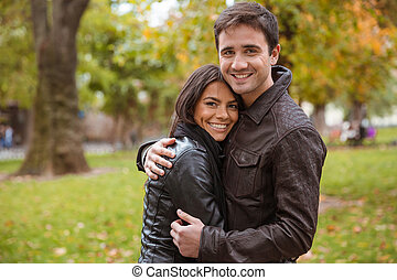 Happy couple hugging outdoors in park