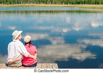 happy couple hugging, view from behind in the background of a beautiful scenic lake