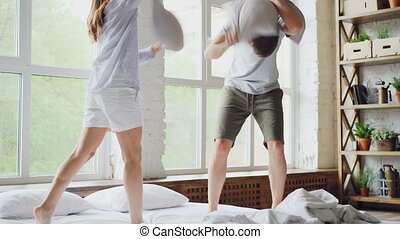 Happy couple husband and wife are having pillow fight on...
