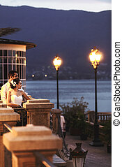 Happy couple husband and wife hugging at balcony in evening near sea