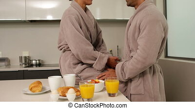 Happy couple in bathrobes chatting