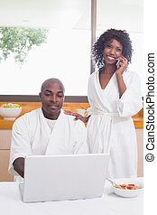 Happy couple in bathrobes in the kitchen using technology at...