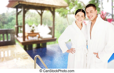 happy couple in bathrobes over spa hotel resort - people,...